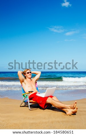 Young Attractive Casual Businessman Entrepreneur Relaxing at the Beach with Laptop Computer  - stock photo