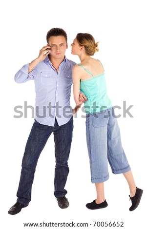 Young attractive casual couple, man talking on the phone, woman whispering in his ear suggesting something, isolated on white background