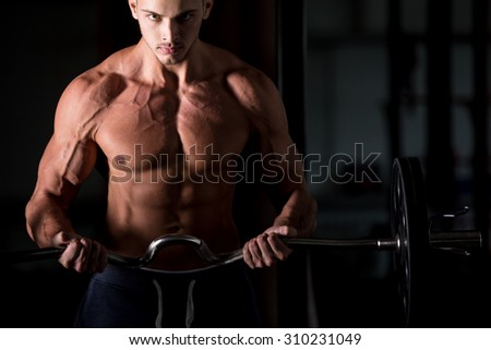 Young attractive caucasian bodybuilder sportsman lifting a barbell in gym, doing biceps training, looking at camera - stock photo