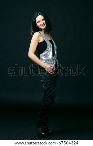 young attractive caucasian brunette female in black trousers and silver top