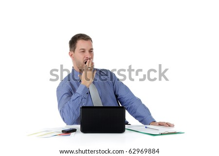 Young attractive caucasian businessman in office at desk, with a laptop and cell-phone and clipboard, looking tired. Studio shot. White background. - stock photo