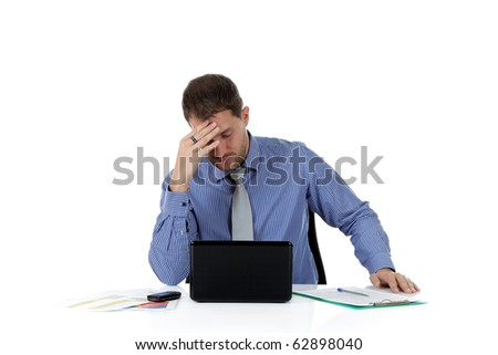 Young attractive caucasian businessman in office at desk, with laptop, cell-phone and clipboard, accusing headache. Studio shot. White background. - stock photo