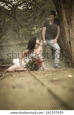 Young attractive caucasian couple flirting on wooden deck with red flowers