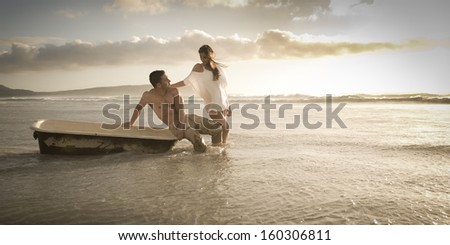 Young attractive caucasian couple on beach with vintage bath tub - stock photo