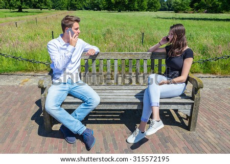 Young attractive caucasian couple on bench calling each other with  mobile phones - stock photo