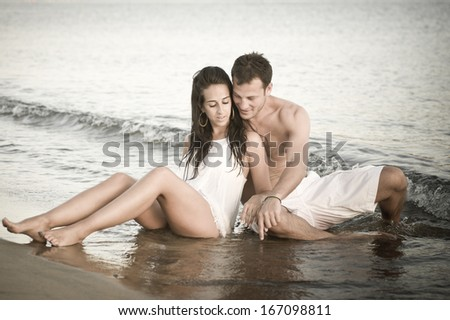 young attractive caucasian couple outdoors sitting on beach in the water flirting