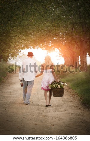 Young attractive caucasian couple walking on dirt road through avenue of trees  - stock photo