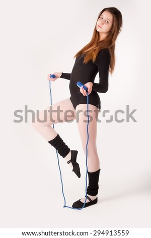 young attractive caucasian girl in black sportswear with jumping-rope on white background - stock photo
