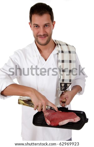 Young attractive caucasian male cook with uniform preparing a tender t-bone steak for grill. Studio shot. White background. - stock photo