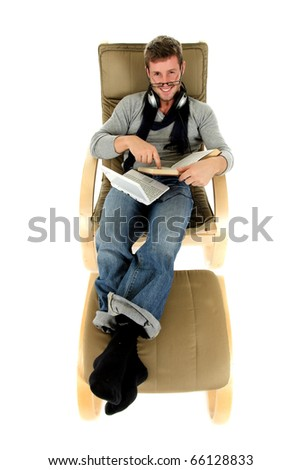 Young attractive caucasian man headset and netbook, wearing spectacles, lying on sofa and reading book. View from high angle. Relaxing time. - stock photo
