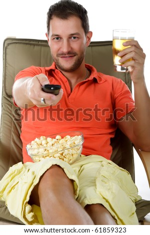 Young attractive caucasian man sitting on sofa with popcorn and holding a glass of beer and a remote control. Studio shot. White background. - stock photo