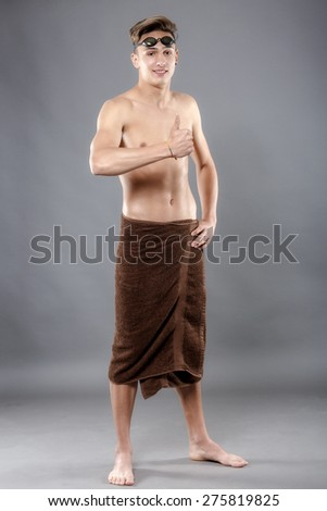 Young attractive caucasian man swimmer with goggles and towel isolated over Gray background - stock photo