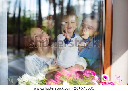 Young attractive caucasian parents and their child are looking into the window outdoor  - stock photo