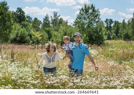 Young attractive caucasian parents and their child have fun outdoor on sunny day