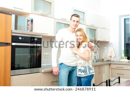 Young attractive caucasian smiling couple hugging posing in their kitchen looking at camera - stock photo
