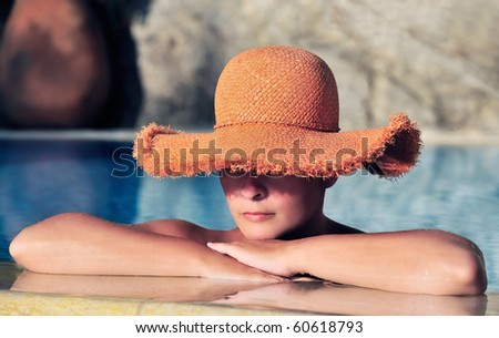 Young attractive caucasian woman in a straw hat, resting by the side of a swimming pool - stock photo