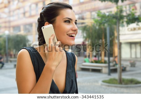 Young attractive cheerful woman calling smart phone, summer outdoor. - stock photo