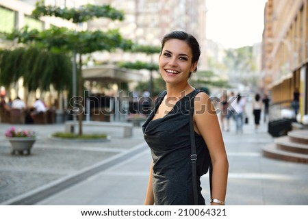 Young attractive cheerful woman walking in city. - stock photo