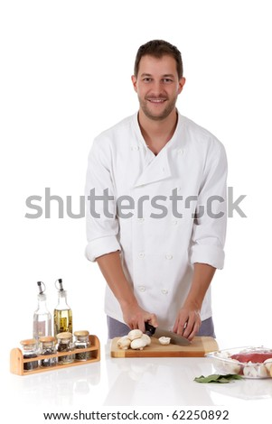 Young attractive chef caucasian male with uniform cutting fresh mushrooms for a tasty roast beef. Studio shot. White background. - stock photo