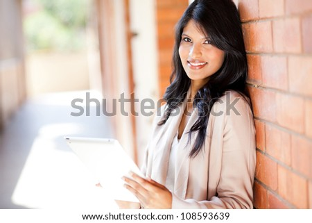 young attractive college girl using a tablet computer - stock photo