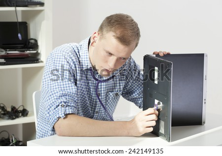 Young attractive computer science healing broken laptop - stock photo