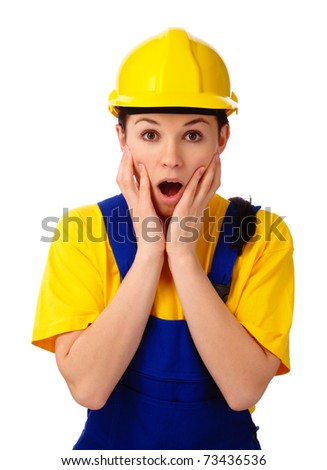 Young attractive construction girl holding her face in astonishment, isolated over white - stock photo
