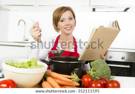 young attractive cook woman preparing vegetable stew soup reading recipe cookbook at domestic kitchen smiling happy and satisfied in healthy nutrition and lifestyle concept - stock photo