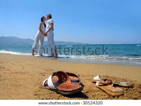 Young attractive couple at the beach (focused front view) - stock photo