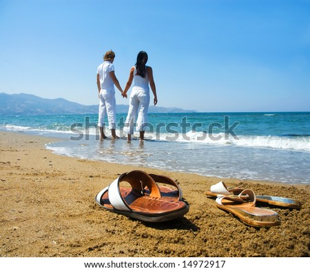 Young attractive couple at the beach holding hands (focused front view)