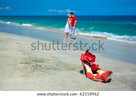 Young attractive couple at the beach kissing (focused front view) - stock photo