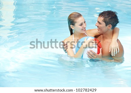 Young attractive couple bathing with beach ball in swimming pool - stock photo