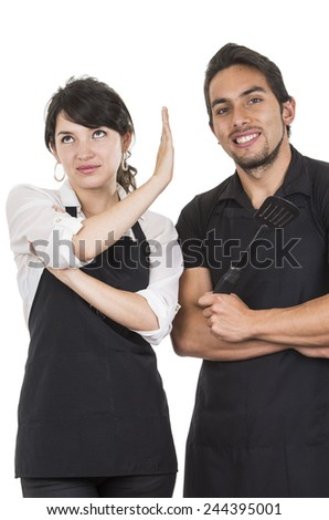 young attractive couple chefs wearing black apron isolated on white - stock photo
