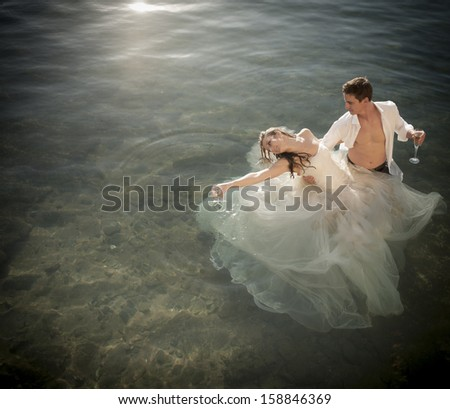 Young attractive couple dancing in pool of water with champagne glasses - stock photo