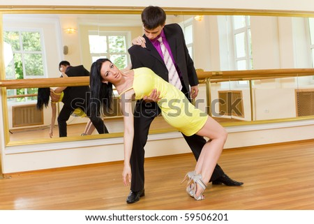 Young attractive couple dancing on the background of mirrors - stock photo