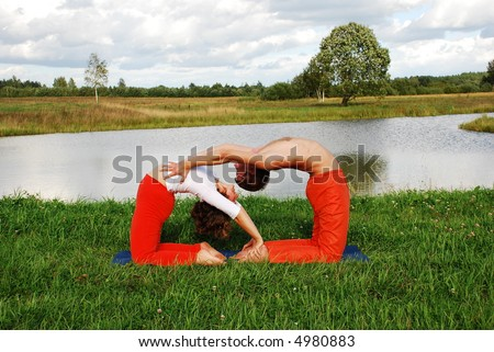 Young attractive couple doing yoga together - stock photo