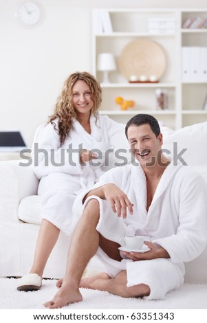 Young attractive couple drinking coffee at home - stock photo