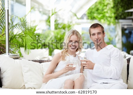 Young attractive couple drinking water in a restaurant - stock photo