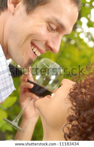 Young attractive couple drinking wine outside among trees