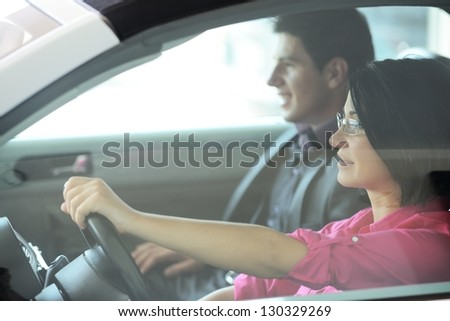 Young attractive couple driving in a car - stock photo