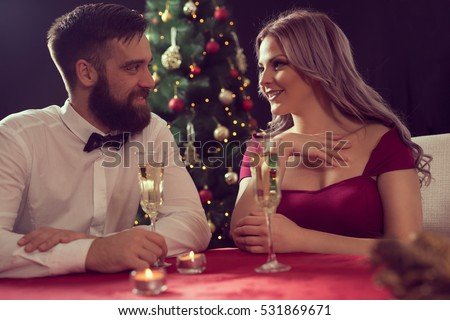 Young attractive couple enjoying romantic Christmas dinner, drinking champagne and making a toast