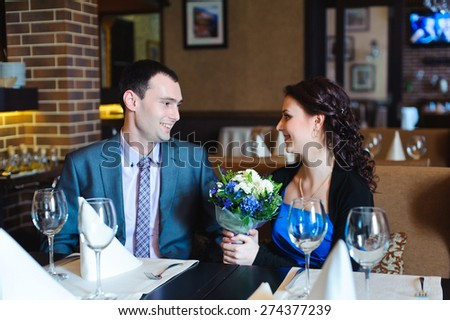 Young attractive couple enjoying sitting together in a restaurant - stock photo
