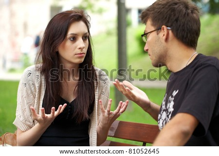 young attractive couple have an argument over something, outdoor shoot - stock photo