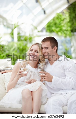 Young attractive couple in a white restaurant - stock photo