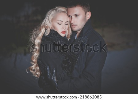 Young attractive couple in black autumn coat - stock photo