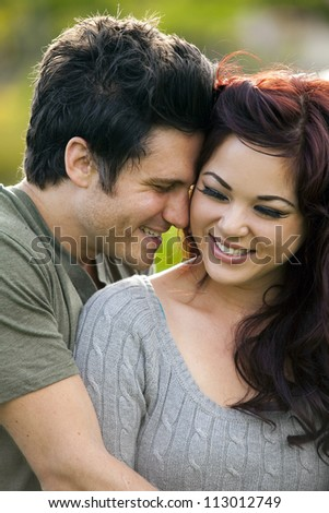 Young attractive couple in love at a park - stock photo