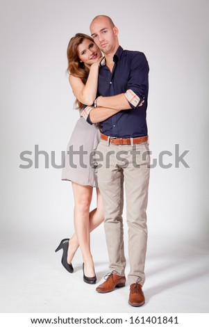 young attractive couple in love embracing portrait on grey backgound  - stock photo