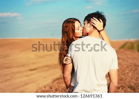 Young attractive couple in love kissing in summer in field. - stock photo