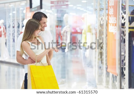 Young attractive couple in shop window - stock photo