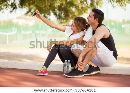 Young attractive couple of runners taking a selfie with a smartphone after working out together - stock photo