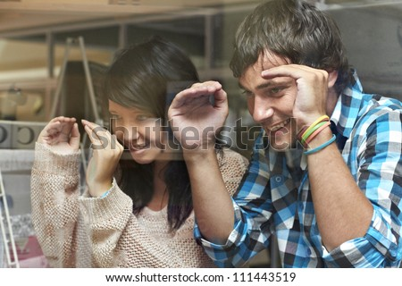 Young attractive couple peeking through a shop window - stock photo